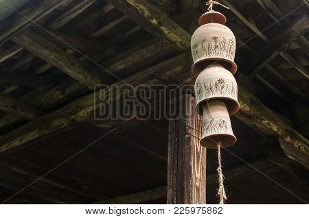 Ceramic Clay Pottery Decorative Garden Wind Chime Bells On A Rope Under Wooden Beams Rustic House Ro
