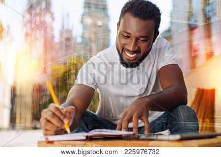 Easy Task. Positive Diligent Student Feeling Excited While Sitting At The Little Table With A Pencil
