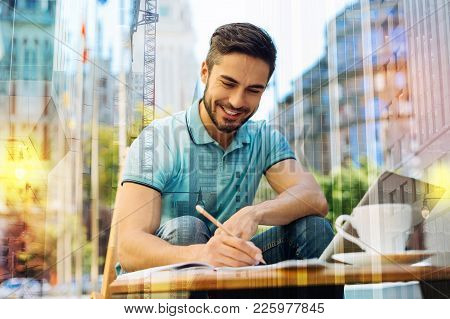 Young Writer. Cheerful Smart Creative Young Author Feeling Excited And Glad While Sitting Alone In A