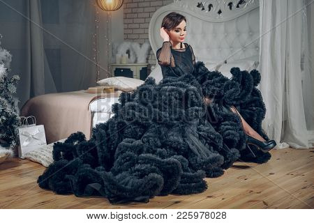 Beautiful Woman In Black Evening Dress Sits On The Bed In Luxury Interior. Fashion Shot. The Girl Is
