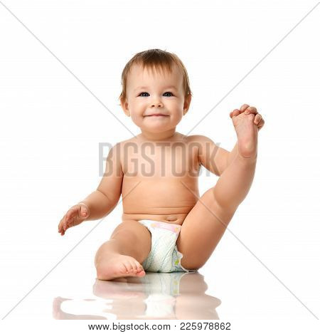 Beautiful Infant Baby Girl Toddler Sitting In Diaper And Hold One Leg Isolated On White Background