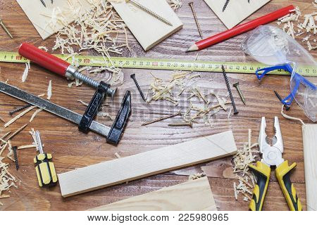 A Carpenter's Tool, Sawdust And Shavings On A Wooden Table. Concept. The View From The Top