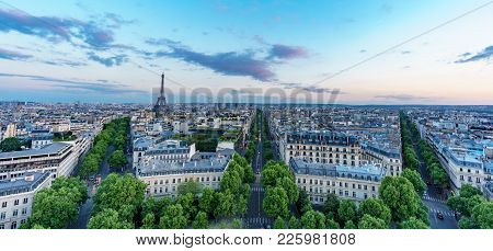 Wide Angle Sunset In The Skyline Of Paris With Eiffel Tower And Wide Streets With Green Trees