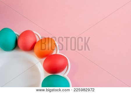 Easter Background. Several Colorful Painted Eggs Are Lying On Wavy White Dish On Bright Pink Paper B
