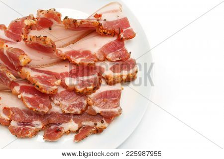 Bacon. Pieces of bacon on a white plate on the table.