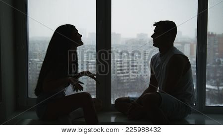 Young Family Couple Sitting On The Windowsill, Emotionally Talking, Arguing And Gesticulating, Relat