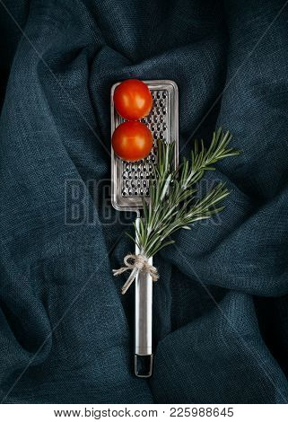 Kitchen Accessory. Metal Cheese Grater With Rosemary And Cherry Tomatoes On Textile Background.
