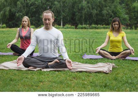 Yoga Athletes In Park - Sportsmen In Lotus Pose, Telephoto Shot