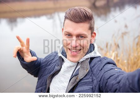 Selfie Of Handsome Blond Man In Front Of Lake In The Cold
