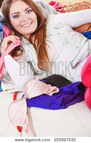 Portrait Of Happy Glad Young Woman Girl Lying On Stack Of Clothes. Disorder And Mess.