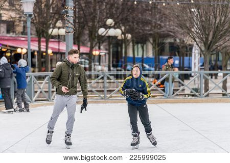 Stockholm, Sweden - February 3, 2018: Front View Of A Young Man And Boy Skating At A Public Ice Skat