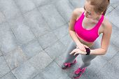 Female runner looking at smartwatch. Athlete using her fitness tracker to see progress or heart rate during cardio workout. Girl training outdoors in city. Technology and active lifestyle concept poster