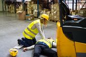 An accident in a warehouse. Woman performing cardiopulmonary resuscitation. poster