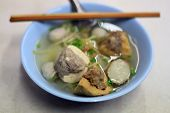 Chinese Food ,  Hakka noodles in a white bowl topping with pork ball fish ball  shrimp ball  fried wontons fried taro minced pork with tofu spring onion vegetable soup , Street food Thailand poster