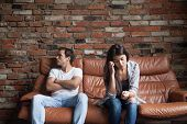 Frustrated upset couple in quarrel not talking after fight, offended stubborn insulted jealous man sitting silent on sofa at home with sad depressed disappointed woman, marriage relationships problem poster