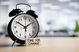 Time for change or action concept message with alarm clock on desk in office