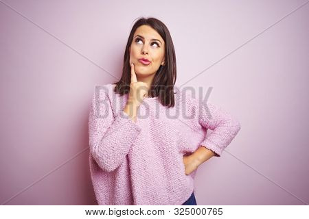 Young beautiful brunette woman wearing a sweater over pink isolated background with hand on chin thinking about question, pensive expression. Smiling with thoughtful face. Doubt concept.