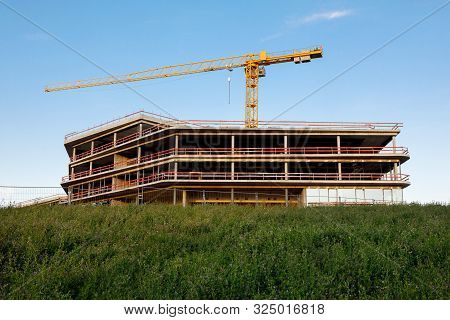 A Construction Crane And A Erected Frame Of The Building Against The Blue Sky. Image Of The Construc