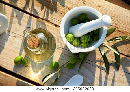 olive oil and green olives on the table