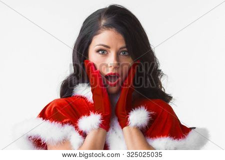 Surprised Christmas woman wearing Santa outfit. Funny closeup portrait of excited woman looking at camera with mouth open in amazement