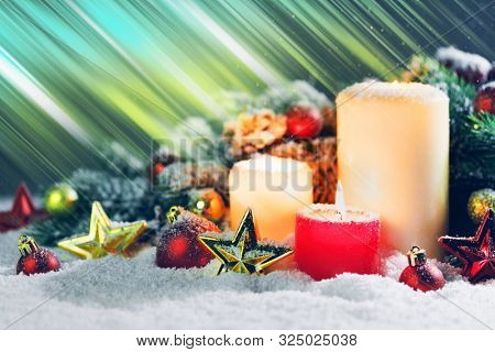 Burning christmas candles with red and golden decorative stars , baubles , pine cones and green branches on snow