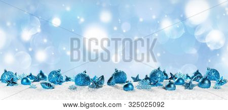 Christmas border with blue ornaments on snow on light bokeh background