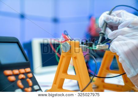 Fixing electronics PCB board in service /  workbench with electronics measuring instruments