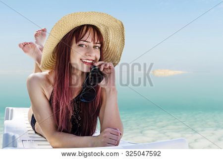 A Young Woman In A Straw Hat Lying On A Chaise Longue, Resting On The Dead Sea In The City Of Ein Bo