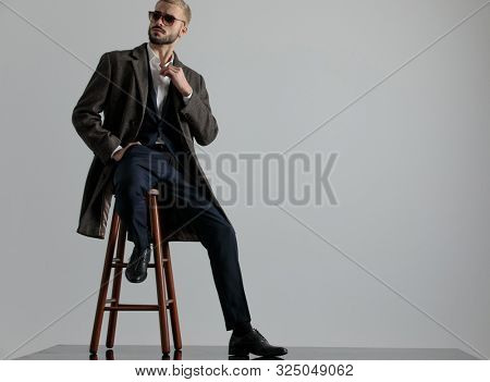beautiful formal business man wearing a navy suit,coat,sunglasses sitting with one leg resting on a chair and one hand in pocket while looking to a side intrigued on gray studio background