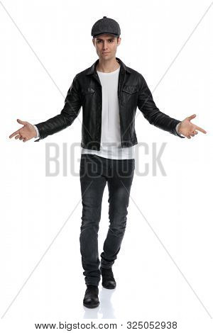 charming casual man wearing a black leather jacket and hat walking with open arms intrigued against white studio background