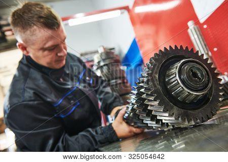 Truck repair service. serviceman works gear shaft of gearbox