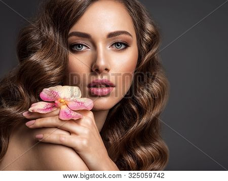 Stunning girl holds flower near eyes. Beautiful woman with brown hair. Woman with beauty long curly  hair. Closeup portrait of a caucasian female. Stunning girl. Skin care concept.
