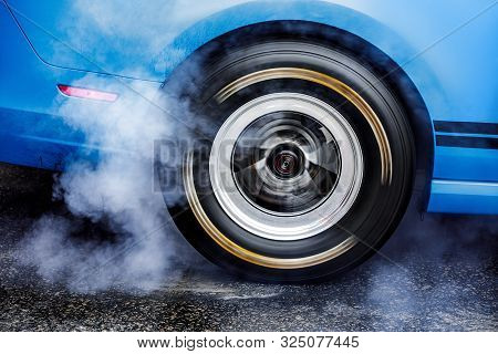 Drifting Car. Drag Racing Car Burns Rubber Off Tires Before The Start