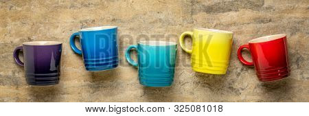 row of colorful stoneware coffee cups against textured handmade bark paper, cofee break concept, long banner