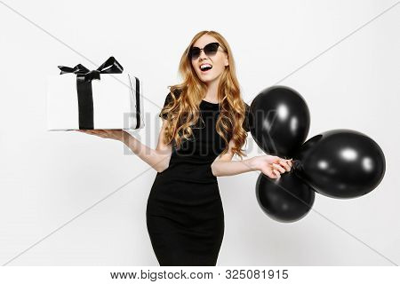 Happy Elegant Young Girl In Black Dress Happily Holding Gift With Black Friday Ribbon And Black Ball