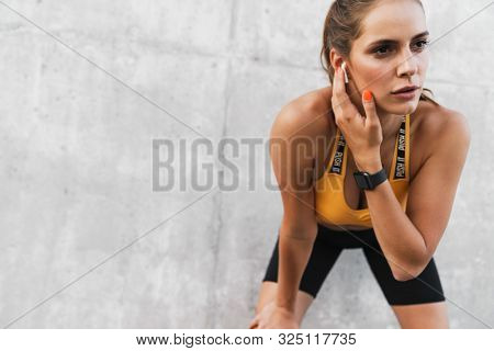 Image of athletic woman looking aside and touching earpods while standing over concrete wall outdoors