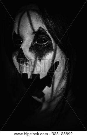Spooky Pumpkin Face Of A Halloween Creature With Opened Mouth On Black Background. Close-up Monochro