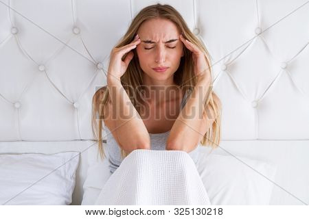 Beauty, Young Woman With Headache. Upset Woman Having A Migraine Lying On A Bed At Home