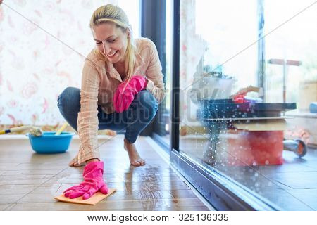 Cleaning lady wipes the parquet floor with a wiping cloth during spring cleaning