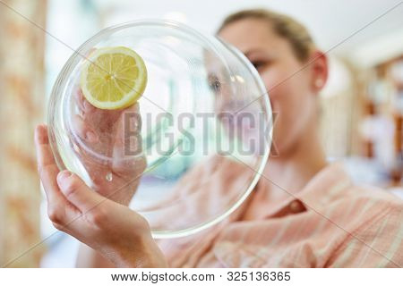 Housewife or maid cleans glass of citric bowl as a home remedy