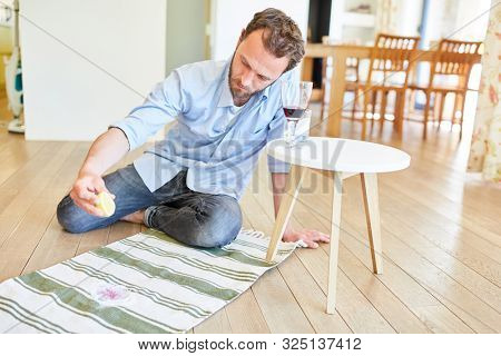 Man as a houseman uses citric acid to remove red wine stain