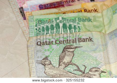 A Close Up Of The  Crrency Of Qatar Or  The Qatari Riyal Notes Of Cash Spread Out On The White Backg
