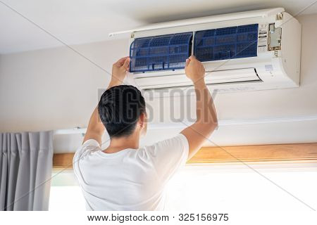 Technician Man Repairing ,cleaning And Maintenance Air Conditioner On The Wall In Bedroom.on Site Ho