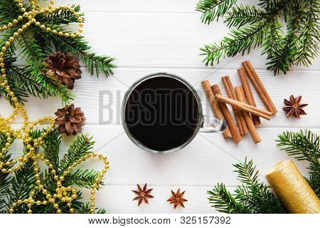 A Cup Of Hot Aromatic Mulled Wine With Spices, Golden Christmas Decoration On White Table, Top View.