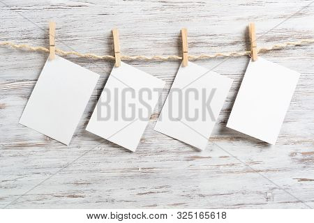 Blank Sheets Of Paper Hanging On Rope On Wooden Background. Vintage Romantic Composition With Copysp