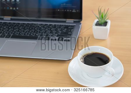 Laptop Computer And Note Paper With Coffee Cup On The Wooden Table