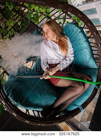 Girl Smokes Hookah In A Wooden Chair