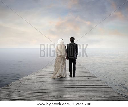 Married couple standing on a wharf over the sea