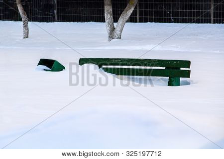Wooden Bench In The Garden Of The House In Winter Under The Snow, Inaction Of Snow Blowers In The Sn