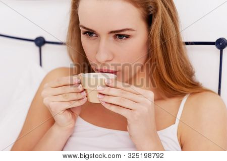Woman drinking coffee while sitting in bed in morning. Relaxing in bed.